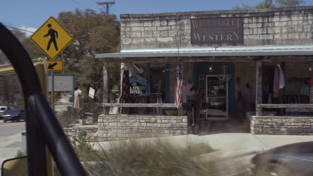 moving car passes by texas western stores and retail shops - centro commerciale suburbano video stock e b–roll