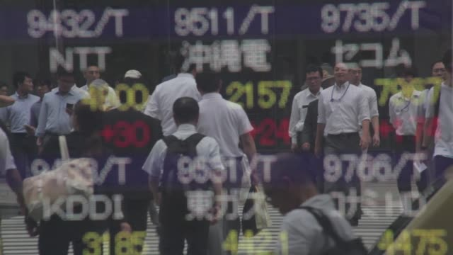 moving clouds and office buildings are reflected in an electronic stock board outside a securities firm in tokyo japan on thursday july 14... - moving office stock videos and b-roll footage