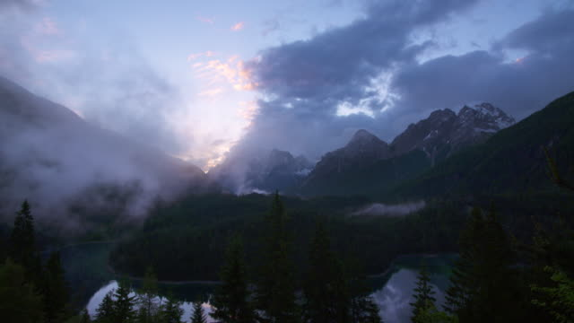 vídeos de stock, filmes e b-roll de moving clouds at sunrise with view over lake blindsee to the mountain zugspitze at fernpass. - montanhas wetterstein