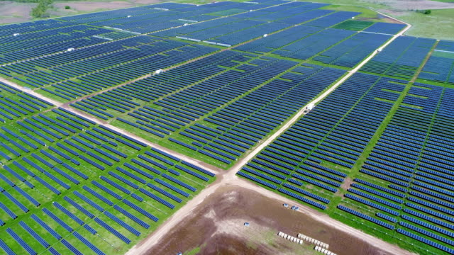 vídeos de stock, filmes e b-roll de movendo para baixo acima de painel solar power plant, fornecendo energia limpa renovável para ajudar a lutar contra a mudança climática e criar empregos - moving activity