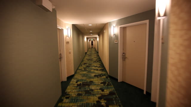 ms pov moving down hotel hallway / wickenburg, arizona,usa - 方向標識点の映像素材/bロール