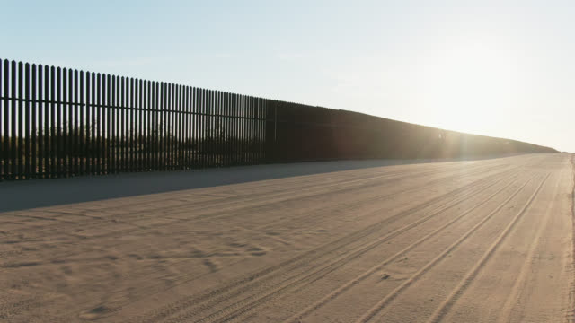 moving drone shot along a dirt road next to the steel-slat border wall (on the us side) between mexico and the united states on a bright, clear, sunny day - international border barrier stock videos & royalty-free footage