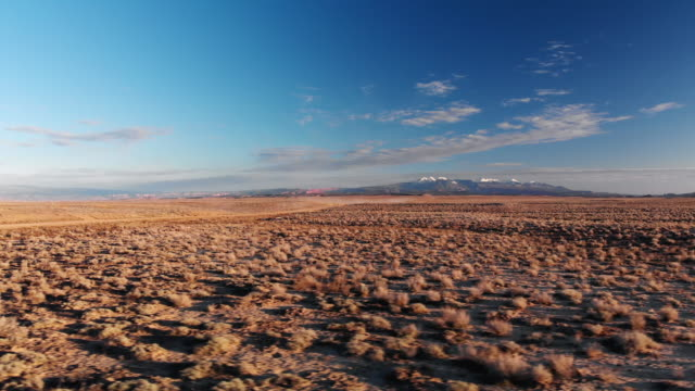 Moving Drone Shot of Desert Plains with Mountains in the Background Outside of Moab, Utah Underneath a Blue Sky at Sunset/Sunrise