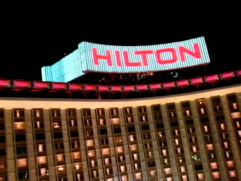 moving fast from edge of parking lot toward hilton hotel w/ spotlights moving on building, steep ascension, hilton roof sign, front of building while... - las vegas hilton stock videos & royalty-free footage