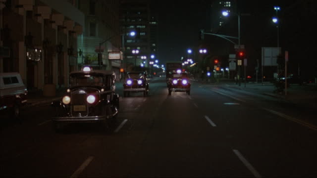 Moving POV of five 1930s vehicles being driven down New York City streets at night.