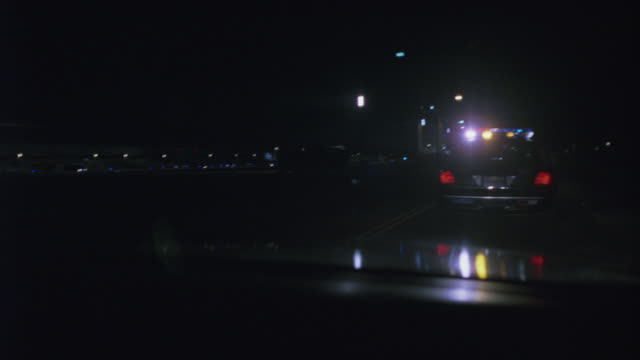 moving pov following a police car with lights flashing as it turns into an airport and searches with spotlights. - los angeles police department stock videos & royalty-free footage