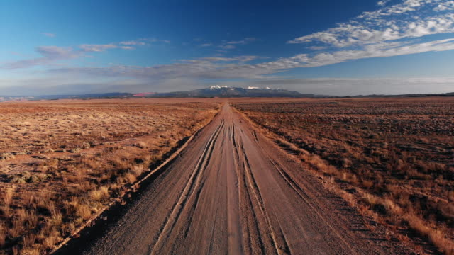 moving forward aerial drone shot of a vanishing point dirt road with mountains in the background outside of moab, utah with desert plains on either side underneath a blue sky at sunset/sunrise - moab utah stock videos & royalty-free footage