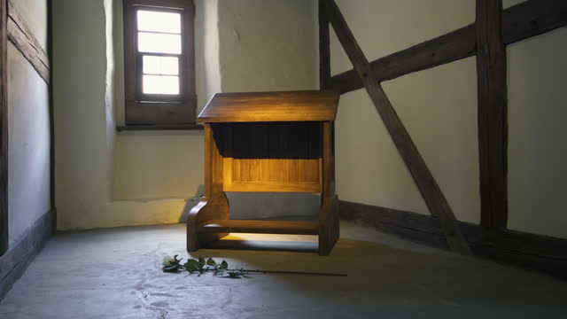 moving forward and into a small prayer room in an old german monastery with a single wooden prayer kneeler, a white rose, dramatic lighting, and old timber framed walls - erfurt, germany - single rose stock videos & royalty-free footage