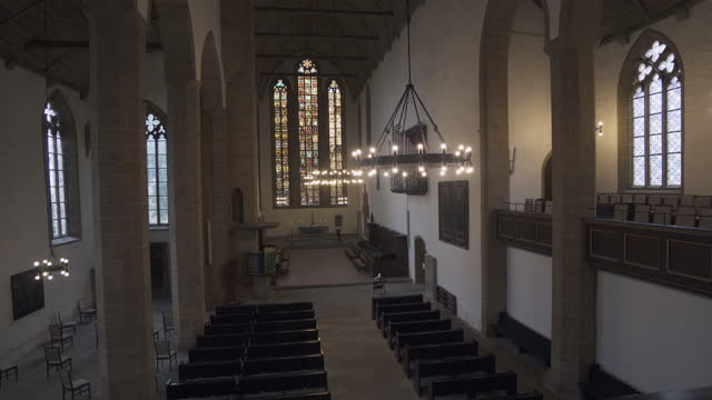 moving forward and panning the full interior length of an old german church with soaring stained glass windows, pews, vaulted ceiling, and stone carvings - erfurt, germany - apse stock videos & royalty-free footage