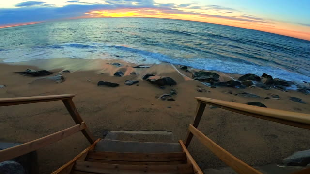 Moving forward footage going down from stairs in a nice beach during sunrise in the Mediterranean Sea with nice colors.