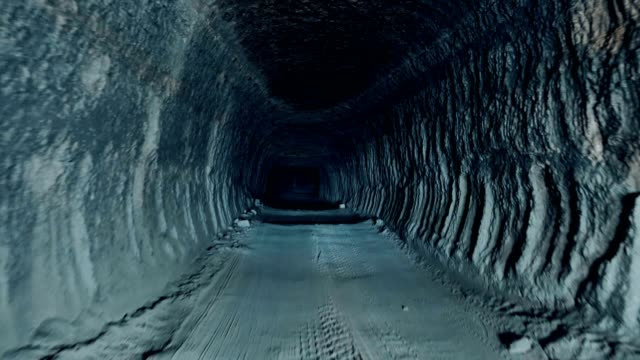 moving forward through a dark cave tunnel - mining natural resources stock videos & royalty-free footage