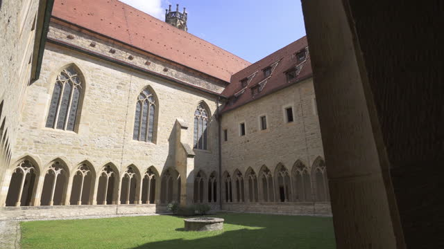 vídeos de stock e filmes b-roll de moving forward through a tall arcade archway into the courtyard of an old german monastery, with stone carving, sandstone bricks, stained glass windows, and bright reflected sunlight - erfurt, germany - arenito