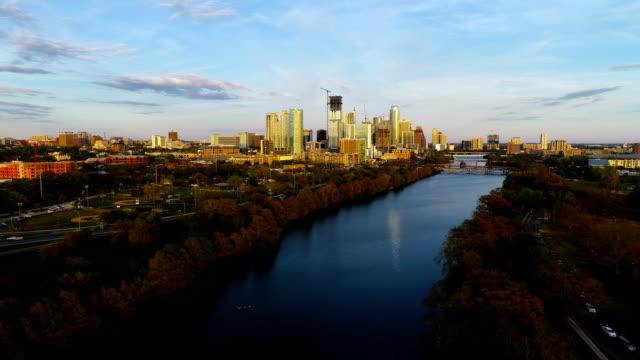 vídeos de stock e filmes b-roll de moving forward towards austin texas usa downtown skyline cityscape above town lake at sunset - town