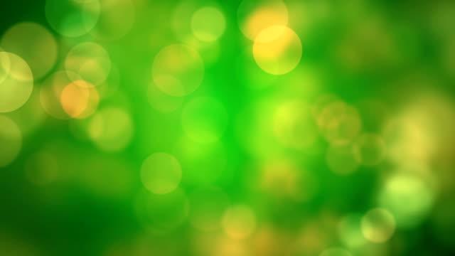 stockvideo's en b-roll-footage met verplaatsen van groen, gele glitter verlichting, intreepupil lichtreflecties loopbare bokeh achtergrond - langzaam