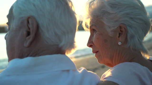 vídeos de stock, filmes e b-roll de moving handheld camera from a back view of a senior couple seating on a beach chair at the sunset. - homens idosos