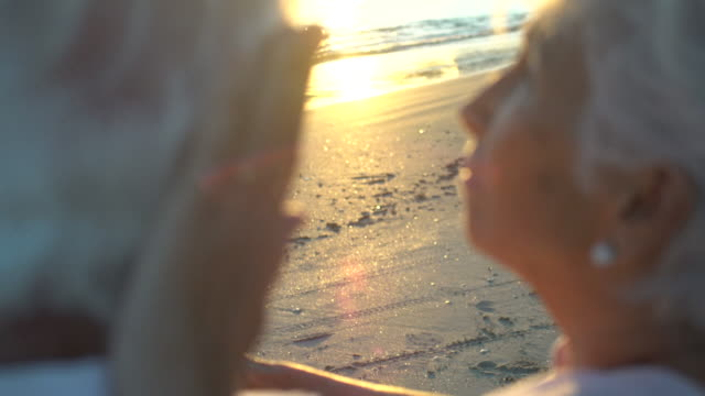vidéos et rushes de moving handheld camera from a back view on cu of senior couple with tenderness at the beach chair with the sunset on flair lenses. - affectueux