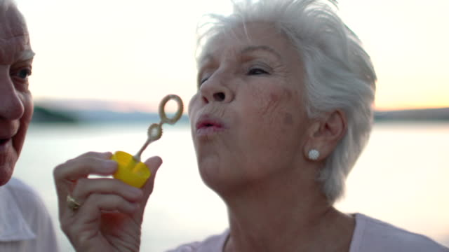 vídeos de stock, filmes e b-roll de moving handheld camera of a couple of seniors having fun and  laughing, blowing bubbles at the beach. - 70 anos