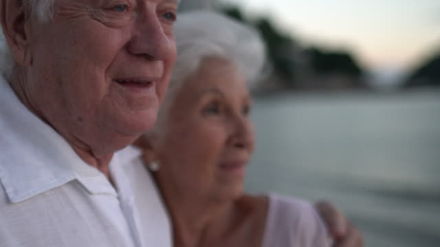 vídeos de stock, filmes e b-roll de moving handheld camera of a seniors couple hugging and laughing at the sunset on the beach. - homens idosos