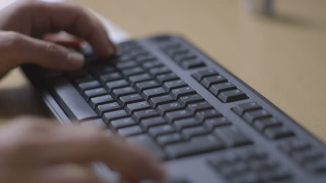 moving handheld shot of hands using keyboard - desktop pc stock-videos und b-roll-filmmaterial