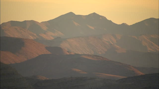 vidéos et rushes de moving in shadow beside mccullough mountains angled sunlight on slopes of range beyond misty shadows - nevada