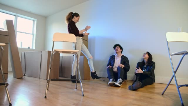 moving in! the group of young friends, teenager caucasian white girls, sisters, and latinos teenager boy, sitting on the floor in the empty living room filled with cardboard boxes, in the new house. - 18 19 years stock videos and b-roll footage