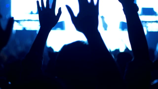Moving Light Show And Silhouette hands of crowd people enjoying the nightlife club party with concert. Blurry night club DJ party for Celebrate event