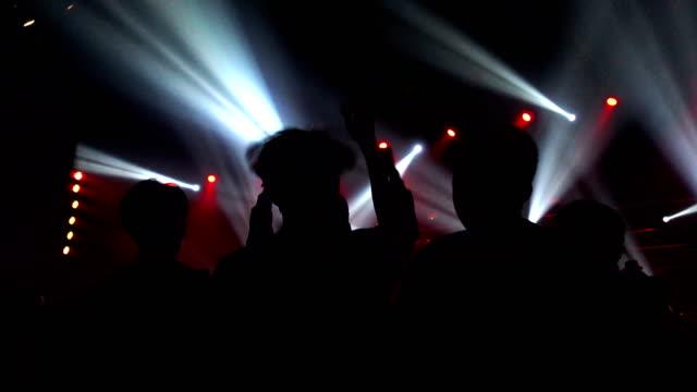 stockvideo's en b-roll-footage met bewegende lichtshow en silhouet handen van menigte mensen genieten van het nachtleven club partij met concert. wazig nachtclub dj partij voor celebrate evenement - club dj