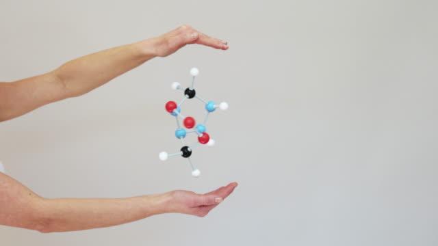 Moving molecule model between hands.