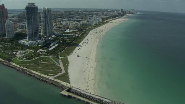 moving north, fisher island w/ condominiums, apartment buildings, biscayne bay, government cut shipping canal, south beach skyscrapers,... - biscayne bay stock-videos und b-roll-filmmaterial