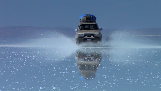ws pov suv moving on flooded salar de uyuni creating splashes / daniel campos, potosi, bolivia - ウユニ塩湖点の映像素材/bロール