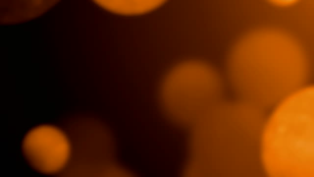 moving orange bokeh, glitter lights, defocused light reflections loopable 4k background video for concepts of love, christmas, party-social events, celebration events, birthday events - orange colour stock videos & royalty-free footage