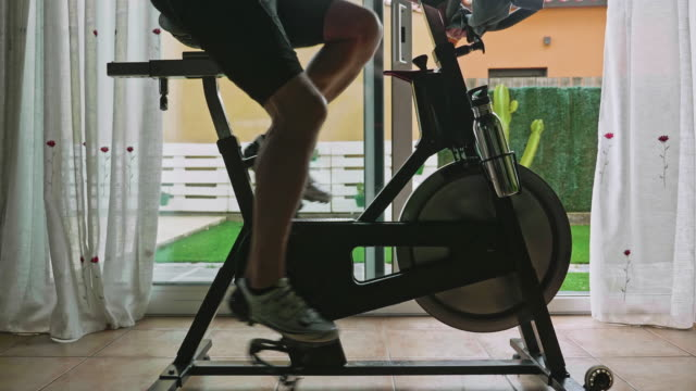 moving out video of man working out on exercise bike at home - home workout stock videos & royalty-free footage