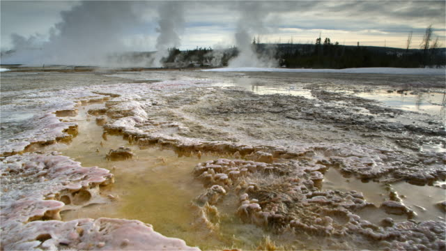 pov moving over hot springs at yellowstone caldera, yellowstone national park, wyoming, usa - イエローストーン国立公園点の映像素材/bロール