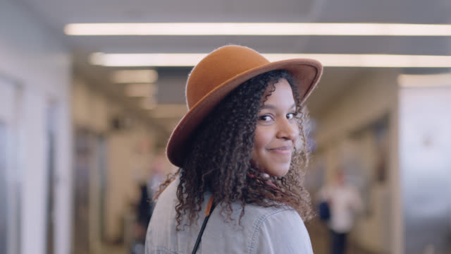 SLO MO. Moving portrait of hip young woman in hat walking through airport terminal.