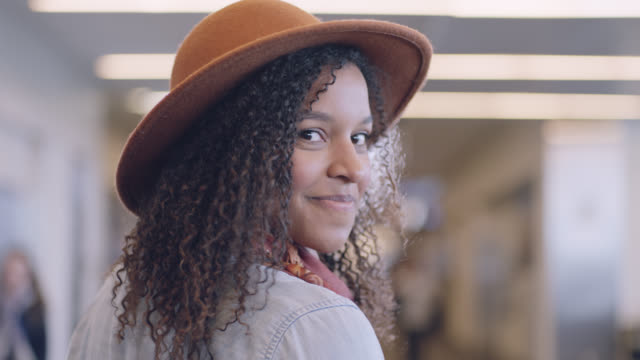 slo mo. cu. moving portrait of smiling young woman in hat walking through airport terminal. - hut stock-videos und b-roll-filmmaterial
