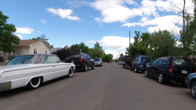 moving process plate of a vehicle driving along a road in a residential district with vehicles parked along the curb under a partly cloudy sky - western usa stock videos & royalty-free footage