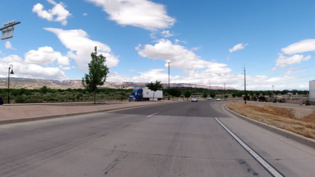 moving process plate of a vehicle driving along a road in grand junction, colorado with the colorado national monument in the background underneath a partly cloudy sky - road marking stock videos & royalty-free footage