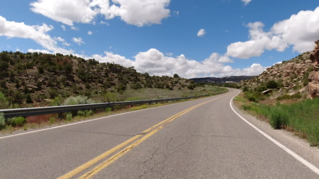 moving process plate of a vehicle driving up an incline to the high desert of the colorado national monument near grand junction, colorado under a partly cloudy sky - road marking stock videos & royalty-free footage