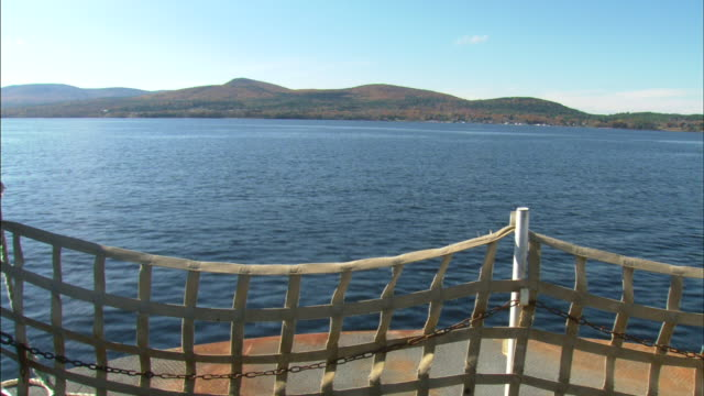 Bow of ferry moving over calm blue water safety net lower frame FG island w/ hills BG clear blue sky