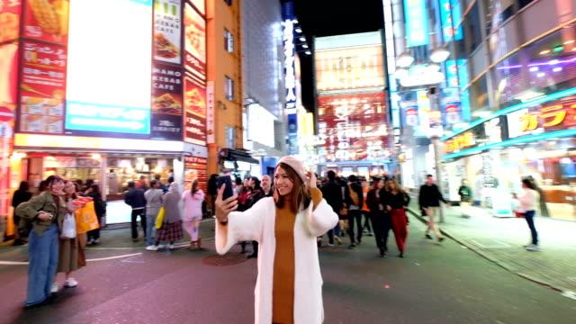 4 k 動画撮影: 多くの夜の街を歩く渋谷で携帯カメラを用いたアジアの女性 selfie 看板背景。渋谷東京ランドマーク - ティーンエイジャー点の映像素材/bロール