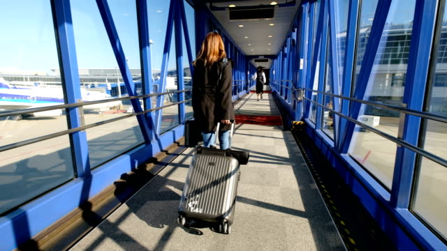 vídeos de stock e filmes b-roll de 4k moving shot: asian woman dragging luggage in aircraft docking at international airport. when she arrived the destination - bagagem