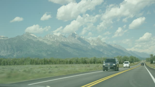moving shot from the perspective of a car driving along a highway running parallel to the grand teton mountains in grand teton national park in western wyoming on a sunny day - grand teton stock videos & royalty-free footage