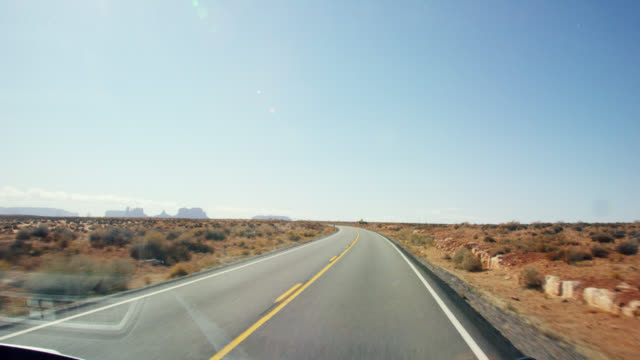vídeos de stock e filmes b-roll de moving shot from the perspective of a vehicle of a road while driving down a highway/interstate in the desert of arizona on a bright, sunny day with mountains and rock formations in the distance - céu claro
