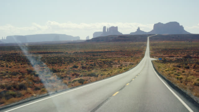moving shot from the perspective of a vehicle of a road while driving down a highway/interstate in the desert of arizona on a bright, sunny day with mountains and rock formations in the distance - monument valley stock videos & royalty-free footage