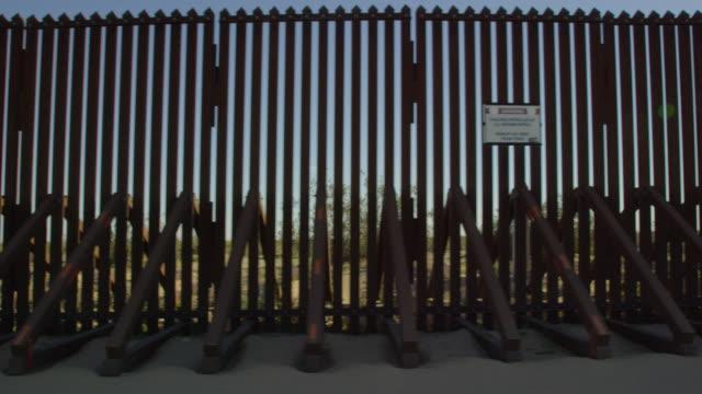 stockvideo's en b-roll-footage met bewegend schot van de kant van een voertuig van de staal-slat grensmuur (de kant van de v.s.) tussen mexico en de verenigde staten op een zonnige dag - sunny