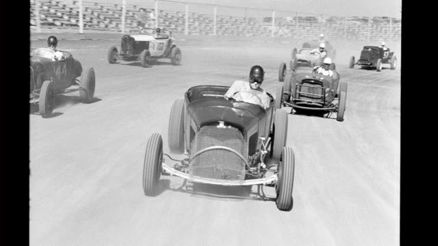 vídeos de stock, filmes e b-roll de moving shot looking backward at hot rods racing on track hot rods and their drivers on january 01 1940 in california - hot rod