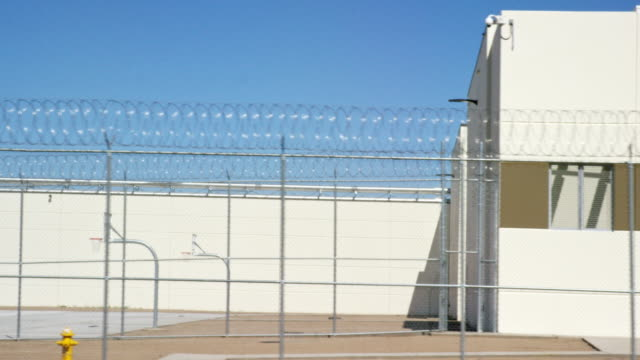 moving shot of a prison in phoenix, arizona with a barbed wire chainlink fence surrounding an outdoors basketball court on a sunny morning - blame stock videos & royalty-free footage
