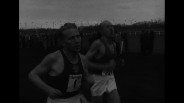 moving shot of crowd of runners / two shots of runners racing past cameras / moving shot of vladimir kuts of the soviet union on left and emil... - atletico video stock e b–roll