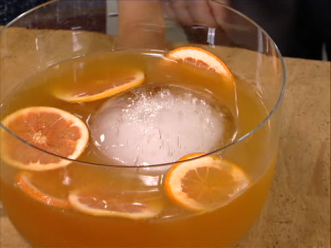 vídeos y material grabado en eventos de stock de moving shot of filled punch bowl close up spreading shot of a mixed drink with fresh oranges in a punch bowl - healthcare and medicine or illness or food and drink or fitness or exercise or wellbeing