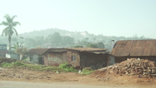 moving shot of street in uganda - village stock videos & royalty-free footage